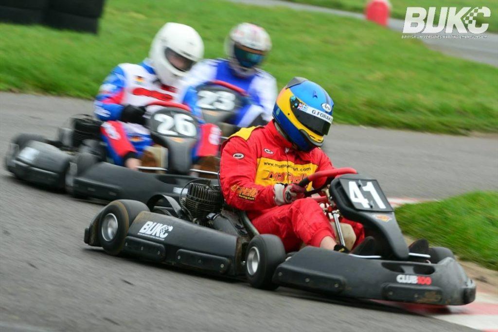 Three men race go karts round a track