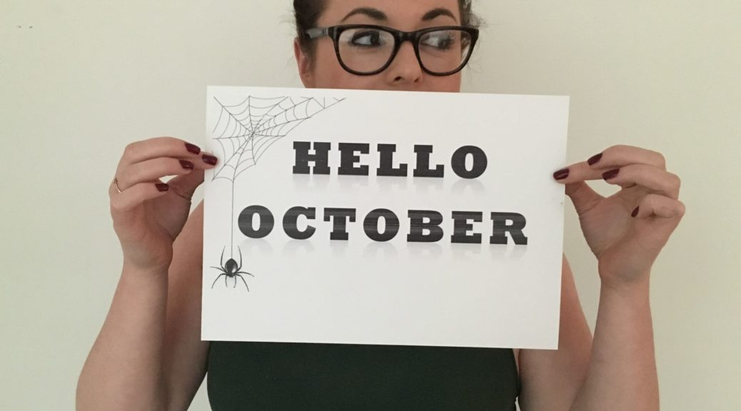 A girl holding a sign that says Hello October