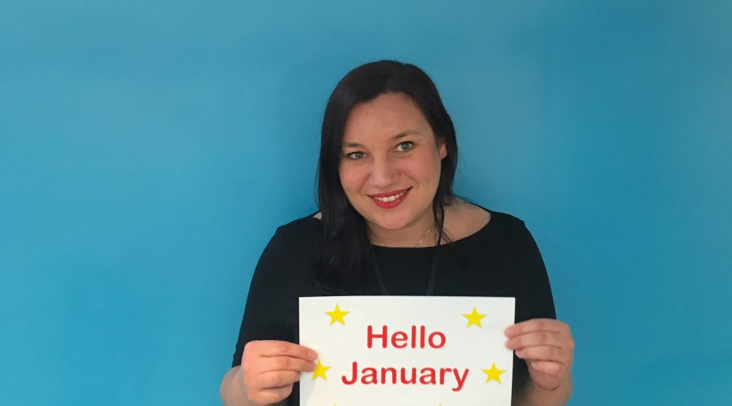 Woman holds a sign saying Hello January