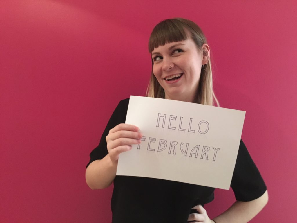 Woman holds sign that reads hello february